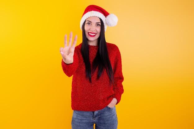 Ritratto felice, sorridente donna che indossa x'mas santa cappello, mostrando tre dita.