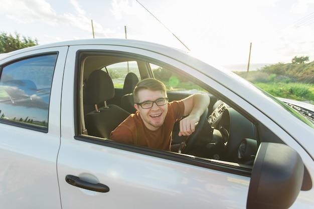 Ritratto di un giovane sorridente felice, acquirente seduto nella sua auto nuova e che mostra le chiavi fuori dall'ufficio del concessionario.