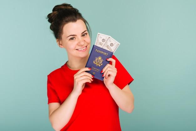 Ritratto di una giovane donna sorridente felice che tiene il passaporto e il denaro del dollaro usa isolato su spazio blu