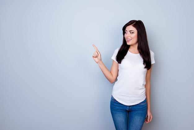 Ritratto di giovane donna sorridente felice che indica sullo spazio della copia e che sta contro lo spazio grigio