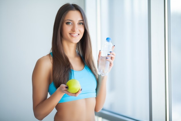 Ritratto di giovane donna sorridente felice con una bottiglia di acqua dolce