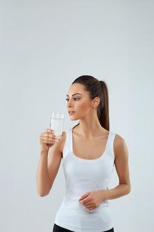 Ritratto di giovane donna sorridente felice con un bicchiere di acqua dolce. assistenza sanitaria. bevande.