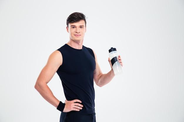 Ritratto di un uomo sportivo felice che tiene in mano una bottiglia con acqua isolata