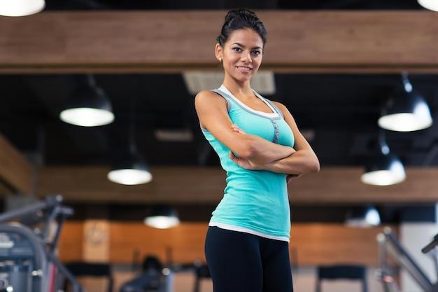 Ritratto di una donna sportiva felice in piedi con le braccia incrociate in palestra