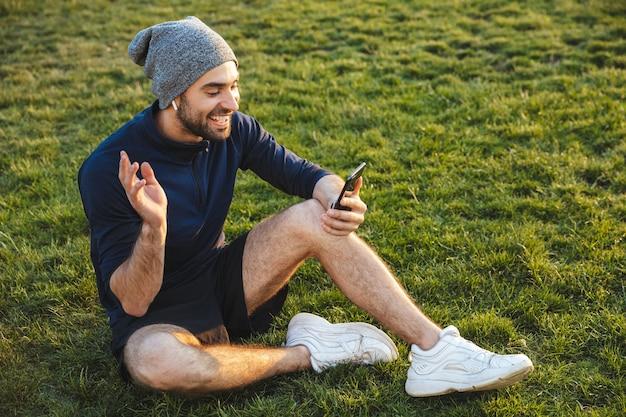 Ritratto di uomo sportivo felice vestito in tuta da ginnastica utilizzando smartphone e seduto sull'erba durante l'allenamento nel parco verde