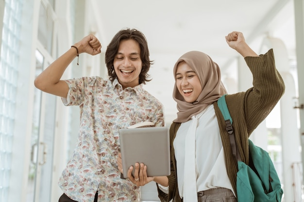 Ritratto di studente felice in possesso di un tablet nel campus. evviva l'abbiamo fatto