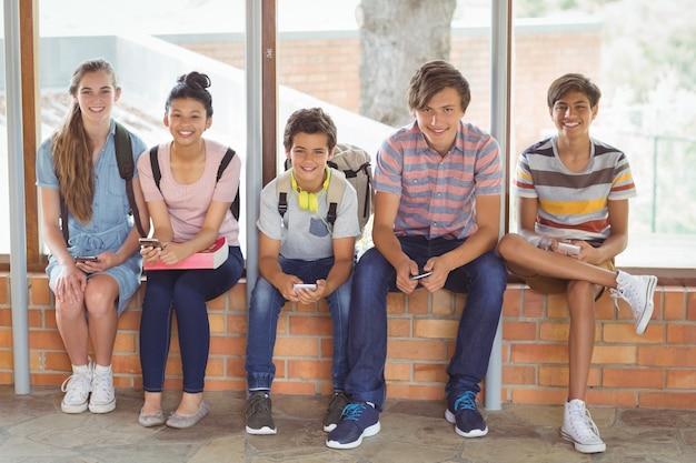 Ritratto di studenti felici seduti sul davanzale della finestra e utilizzando il telefono cellulare in corridoio