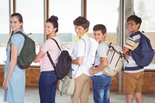 Ritratto di studenti felici in piedi nel corridoio