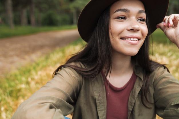 Ritratto di una donna elegante e felice con lunghi capelli scuri che indossa un cappello che guarda da parte mentre si siede sull'erba all'aperto