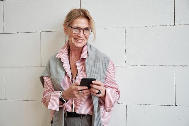 Ritratto di felice riuscita imprenditrice matura con maglione sulle spalle utilizzando il telefono moderno