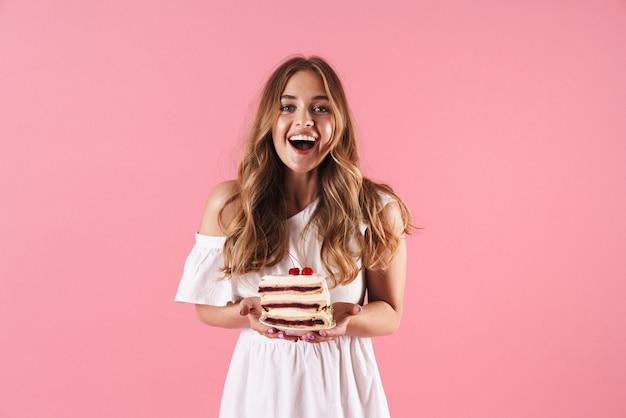 Ritratto di una donna sorpresa felice che indossa un abito bianco che sorride alla telecamera e tiene in mano un pezzo di torta isolato su un muro rosa