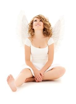 Ritratto di una ragazza adolescente felice angelo sul muro bianco