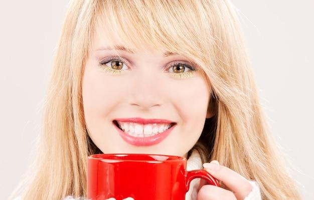Ritratto di felice ragazza adolescente con tazza rossa