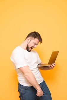 Ritratto di un adolescente felice con la barba in piedi sul giallo
