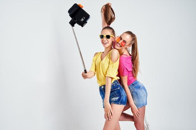 Ritratto di adolescenti felici prendendo selfie insieme isolato su whiteportrait di adolescenti felici in abiti estivi occhiali da sole prendendo selfie insieme isolato su bianco