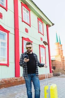 Ritratto di uomo di viaggio felice con la valigia in piedi vicino all'edificio in città