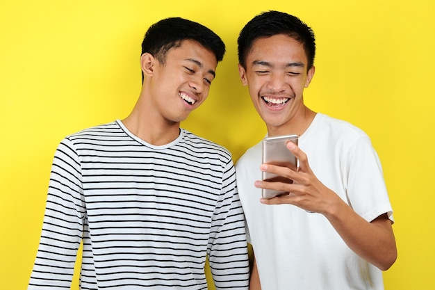 Ritratto di felice due uomini casuali sorridenti guardano smartphone. ritratto di due bei giovani che guardano il telefono e sorridono, su sfondo giallo