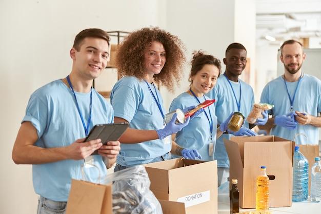 Ritratto di volontari felici che sorridono alla telecamera mentre smistano gli alimenti di imballaggio in scatole di cartone