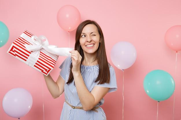 Ritratto di donna felice in abito blu lampeggiante slegare l'arco sulla scatola rossa con regalo presente su sfondo rosa pastello con mongolfiere colorate. festa di compleanno, concetto di emozioni sincere della gente.