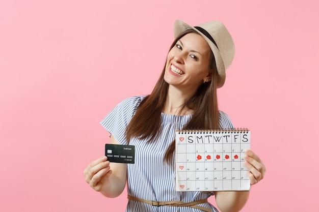 Ritratto di donna felice in abito blu, cappello con carta di credito, calendario dei periodi, controllo dei giorni delle mestruazioni isolati su sfondo rosa di tendenza. concetto ginecologico sanitario medico. copia spazio.
