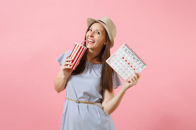 Ritratto di donna felice in abito blu, cappello che tiene una tazza di soda, calendario dei periodi femminili per il controllo dei giorni delle mestruazioni isolati su sfondo rosa. concetto ginecologico sanitario medico. copia spazio