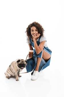 Ritratto di donna felice che beve caffè da asporto mentre è in bilico con il suo cane carlino isolato su un muro bianco