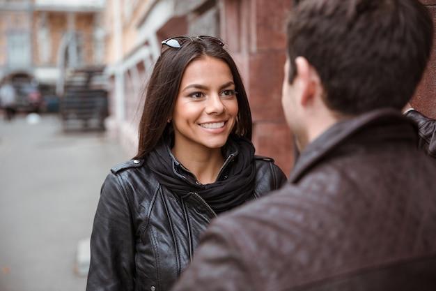 Ritratto di una donna felice che flirta con il suo fidanzato all'aperto
