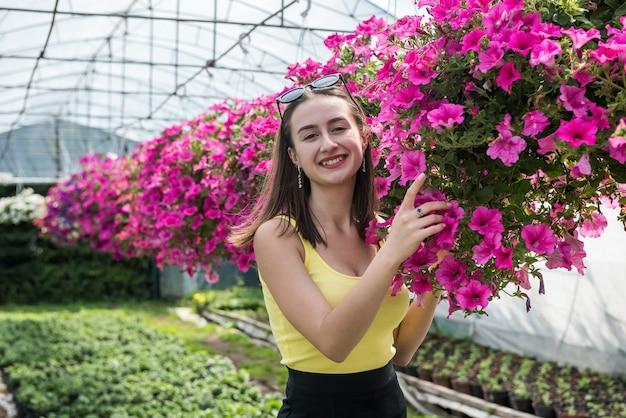 Ritratto di una donna felice proprietario di una serra in posa tra i suoi fiori. fiorista felice in serra