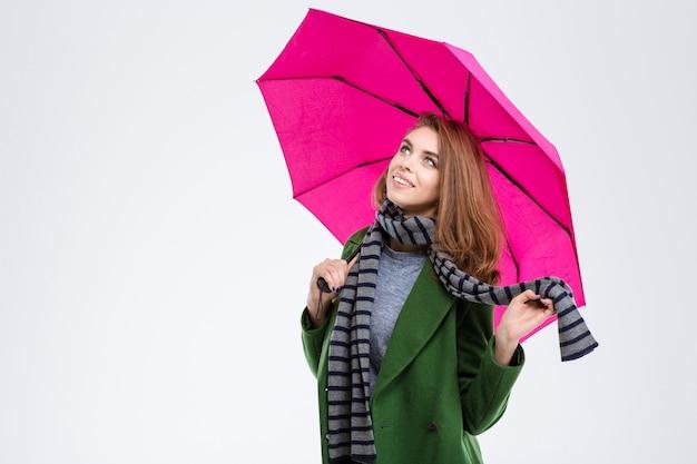 Ritratto di una donna felice che tiene in mano un ombrello rosa isolato su uno sfondo bianco e che guarda in alto