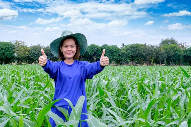 La donna felice del ritratto sta sorridendo il pollice su che esamina la macchina fotografica la fattoria di cereale