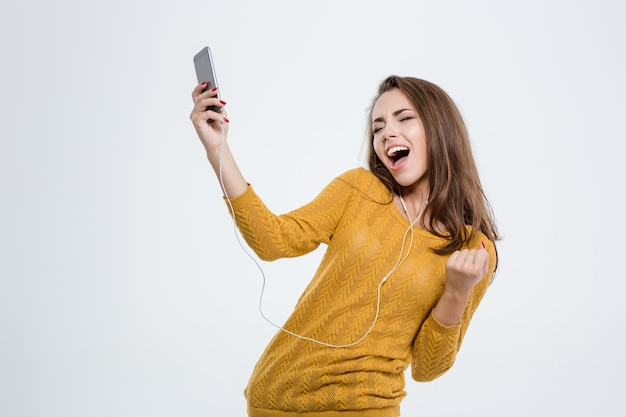 Ritratto di una donna felice che ascolta musica in cuffia e balla isolata su uno sfondo bianco