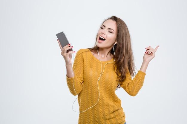 Ritratto di una donna felice che ascolta musica in cuffia isolata su uno sfondo bianco