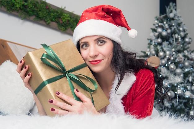 Ritratto di una donna felice in panno di babbo natale che abbraccia molte scatole regalo su sfondo decorato per appartamento di natale. la ragazza con il regalo di natale sul letto è felice e ulybaetsya.