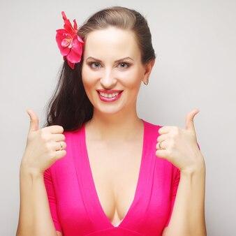 Ritratto di donna felice che mostra i pollici in su