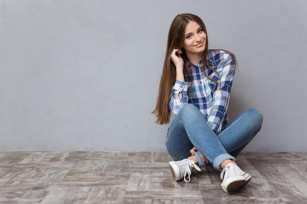 Ritratto di una donna felice seduta sul pavimento su un muro grigio