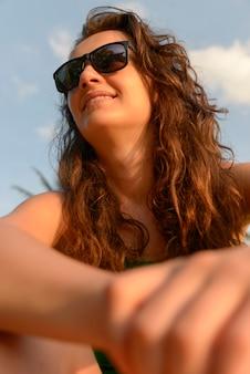Ritratto di una donna felice in occhiali da sole. lei è in spiaggia
