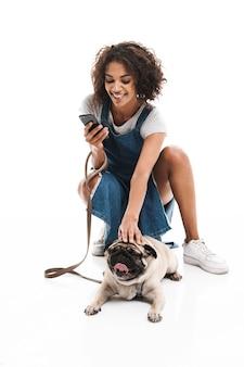 Ritratto di donna felice che usa il cellulare e si accovaccia mentre è in bilico con il suo cane carlino isolato su un muro bianco