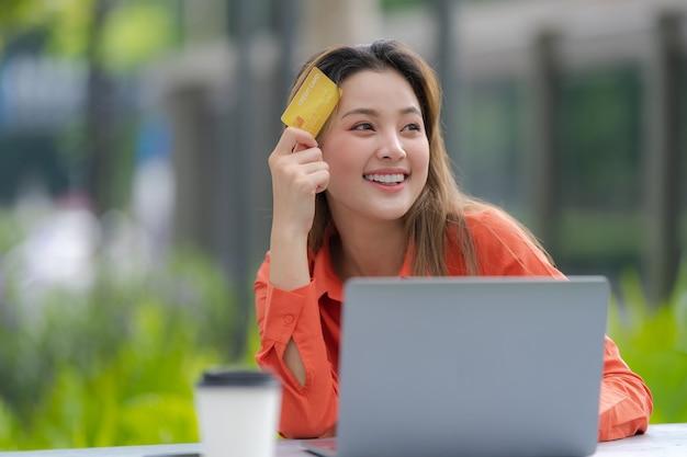 Ritratto di donna felice utilizzando laptop con carta di credito e volto sorridente al parco del centro commerciale