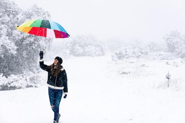 Ritratto di una donna felice che cammina e che tiene un ombrello colorato durante una nevicata.