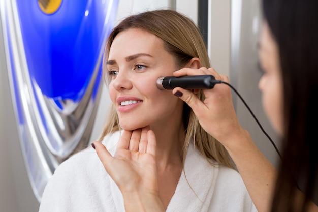 Ritratto di donna felice in abito bianco nel solarium. cosmetologia. solarium verticale. il medico controlla il livello di abbronzatura sulla pelle della ragazza