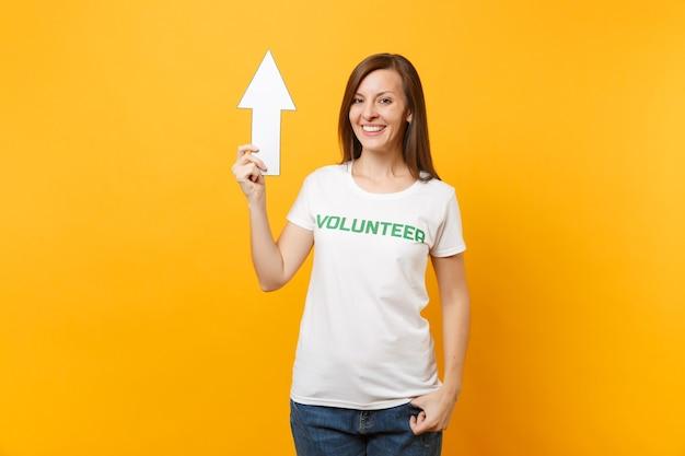 Ritratto di donna felice in t-shirt bianca con scritta iscrizione verde titolo volontario tenere la freccia rivolta verso l'alto isolato su sfondo giallo. aiuto volontario di assistenza gratuita, concetto di lavoro di grazia di beneficenza