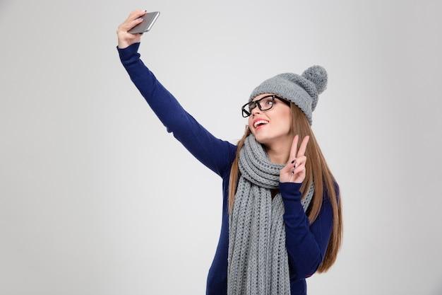 Ritratto di una donna felice in panno invernale che fa foto selfie su smartphone e mostra segno di pace isolato su un muro bianco