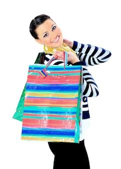 Ritratto di una giovane ragazza adulta felice, con borse con codice colore.