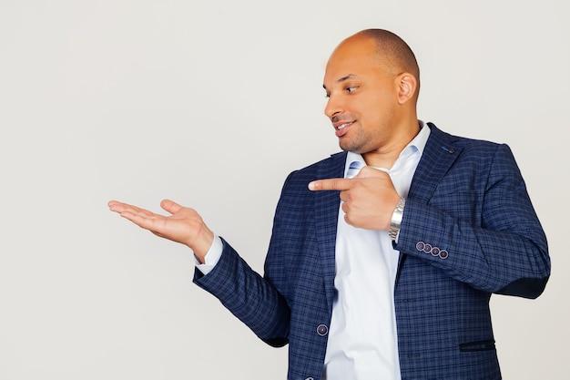 Ritratto di felice giovane ragazzo afroamericano uomo d'affari, stupito e sorridente, mostrando con la mano e indicando con il dito.