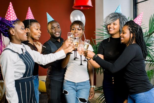 Ritratto di giovani amici africani felici toccando gli occhiali a vicenda e festeggia il compleanno