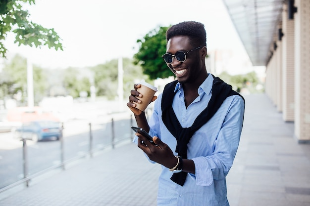 Ritratto di giovane africano felice che chiacchiera al telefono e cammina per strada con una tazza di caffè.