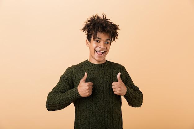 Ritratto di un giovane africano felice vestito con un maglione isolato sul muro beige, dando i pollici in su