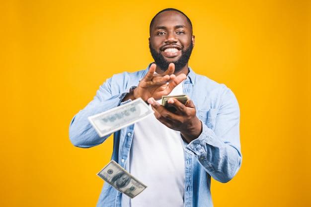Ritratto di giovane uomo afroamericano felice che getta le banconote dei soldi