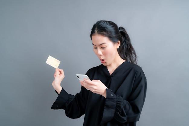 Ritratto di una giovane ragazza asiatica felice che mostra una carta di credito in plastica mentre tiene in mano il cellulare