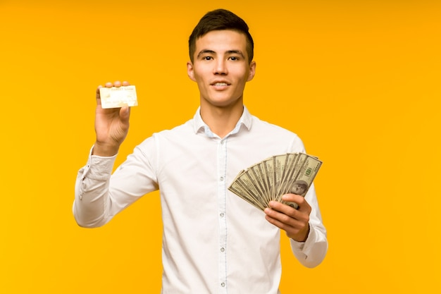 Ritratto di felice giovane uomo asiatico in possesso di carta di credito e soldi in mano sorridendo e guardando la fotocamera su sfondo giallo isolato